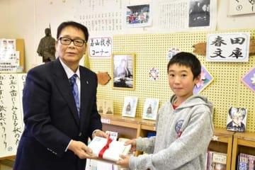 坪谷小児童に牧水の図書を贈呈した春田さん(左)