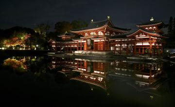 夜間特別拝観が始まる世界遺産・平等院の鳳凰堂。ライトアップされ池の水面に浮かび上がった=16日夜、京都府宇治市