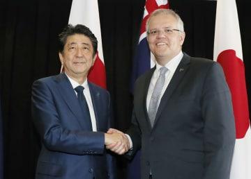 オーストラリアのダーウィンで会談を前に握手するモリソン首相(右)と安倍首相=16日(共同)