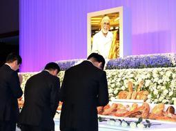 フランスパンが並べられた祭壇に献花する参列者=神戸市中央区港島中町6、神戸ポートピアホテル