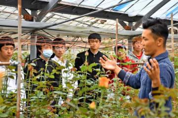 バラ農家の仁田脇さん(右)から栽培方法や6次産業化について説明を受ける参加者=16日午後、宮崎市・仁田脇バラ園