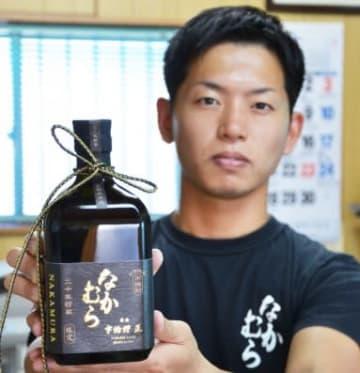 20年間熟成の米焼酎「なかむら」と中村慎弥取締役=霧島市国分湊