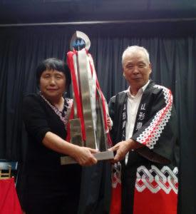 総合優勝を果たした小林さん(左)に優勝トロフィーを授与する篠原会長