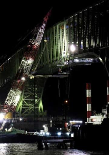 クレーン船で引き上げた補強材を損傷箇所に取り付けた応急復旧工事