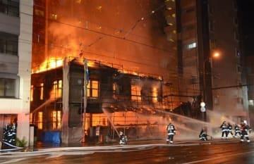 炎を上げて燃える建物に放水する消防隊員ら=16日午後9時半ごろ、熊本市中央区辛島町