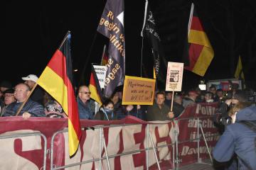 メルケル首相を非難し、怒声を上げる右派のデモ参加者=16日、ドイツ・ケムニッツ(共同)