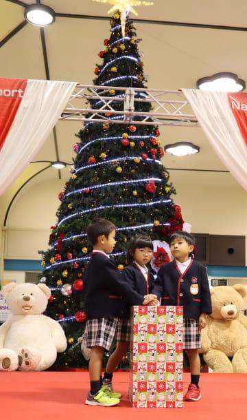 クリスマスツリーのイルミネーションを点灯する園児=長崎空港