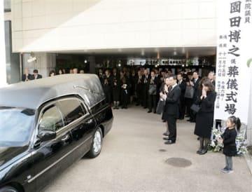 葬儀式場で、園田博之さんの出棺に手を合わせる参列者=16日、東京都港区