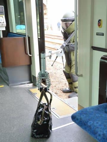 訓練で電車内から不審なかばんを運び出そうとする爆発物処理班の隊員=16日、大阪市住吉区