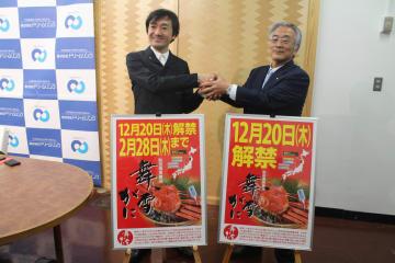 舞雪がに漁解禁をPRするポスターを前に握手する村上社長(左)と菅原市長