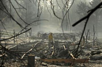 米カリフォルニア州の火災現場で捜索する消防士=16日(AP=共同)