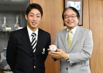 プロ野球ヤクルトスワローズにドラフト指名された久保拓眞さん(左)から深浦弘信伊万里市長にサインボールが贈られた=伊万里市役所