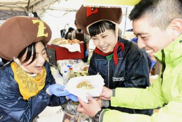 静岡県の代表食材が詰まった「THIS伊豆しいたけバーガーZ」を買い求める来場者(右)=17日午後、鳥取県大山町
