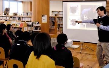 牛鬼など南予の伝統行事や文化と関係する動物について説明する大本敬久さん(右)=17日午前、西予市野村町野村