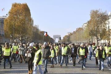 17日、自動車燃料課税引き上げなどに抗議し、パリのシャンゼリゼ大通りでデモをする人たち(共同)