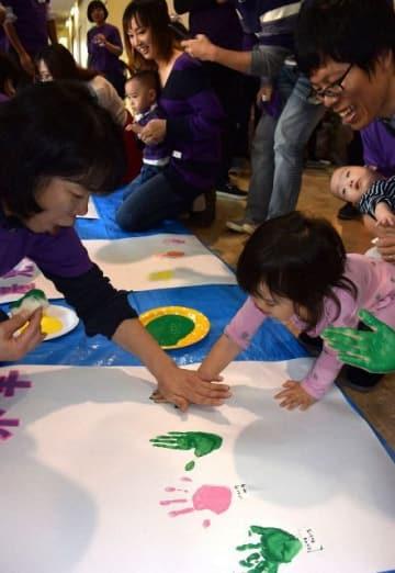 「世界早産児デー」のイベントで、手足でペイントするアートを楽しむ親子=県立こども医療センター