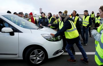 17日、フランス・ナントの道路で車の通行を妨害するデモ参加者(ロイター=共同)