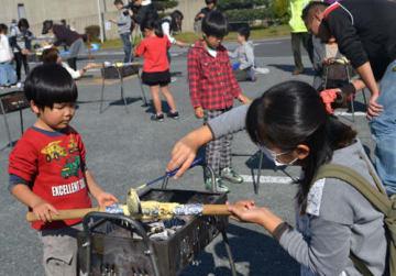 【バウムクーヘン作りを楽しむ親子=亀山市関町泉ヶ丘の関文化交流センターで】