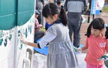 公園の公衆トイレの外壁に手のひらで絵を描く児童ら