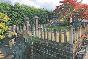 会津藩の降伏後、各地に埋葬されていた戦死者らは改めて寺院に葬られた。阿弥陀寺では、幾重にも遺体が積み重ねられたらしい。周囲より1メートルほど高くなっている墓所に、紅葉から漏れた秋の日が差す=会津若松市七日町