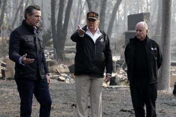 17日、米カリフォルニア州ビュート郡の火災現場で、ブラウン州知事(右)、ニューソム次期知事(左)と話すトランプ大統領(AP=共同)