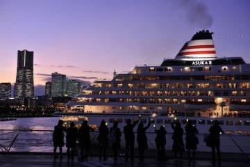 ケミカルライトを手に飛鳥2を見送る修学旅行生。出港すると、目前に夕暮れの景色が現れた=1日、横浜港大さん橋国際客船ターミナル