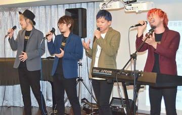 会場の一番後ろで聞く女性に向け、『いつもそばにいるよ』を思いを込めて歌うステイジーのメンバー。右から山本さん、Tatsuyaさん、シートさん、福見健二さん=14日、大阪市北区の大阪府警コミュニティープラザ