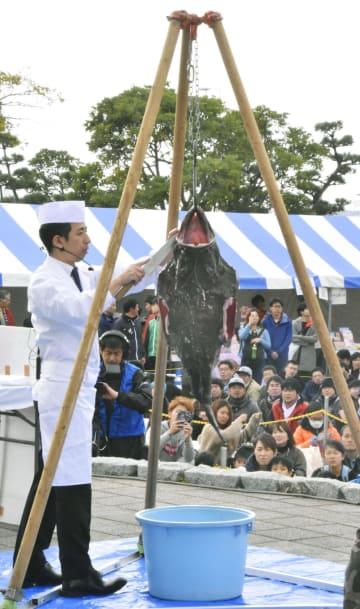 「大洗あんこう祭」でつるし切りを披露する料理人=18日、茨城県大洗町
