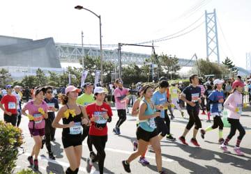 第8回神戸マラソンで力走する参加者。後方は明石海峡大橋=18日、神戸市