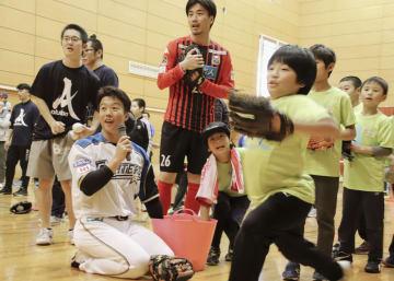北海道厚真町の子どもたちと触れ合う、日本ハムの鶴岡慎也選手(手前左)=18日午後、札幌市