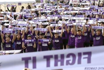膵臓がん啓発のチャリティーイベントで、おそろいの紫のTシャツを着て治療薬開発や早期発見など訴える参加者=18日、東京・日比谷公園