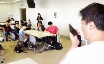「外国人のための防災教室」で通訳を交えた3者通話による119番通報を体験する台湾出身の男性=9月、福井県福井市防災センター