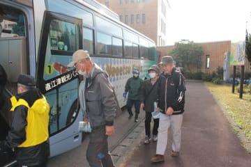 避難経由所へ向かうバスに乗り込む原子力防災訓練の参加者ら=18日、上越市柿崎区