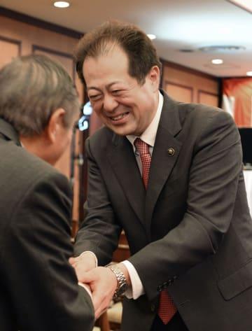 松山市長選で3選を決め、支持者と握手する野志克仁氏=18日夜、松山市