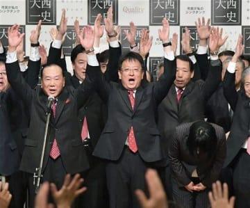 熊本市長選で再選が確実となり、万歳する大西一史氏(中央)=18日午後8時5分ごろ、熊本市中央区のホテル(高見伸)