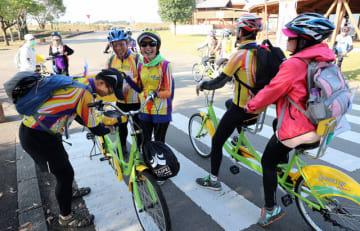 2人乗り用の自転車に乗り込み、出発の準備をする台湾の視覚障害者ら=18日午前、西都市・このはな館前
