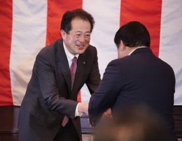 3選を確実にし、支持者と握手する野志克仁さん(左)=18日午後8時25分ごろ、松山市一番町1丁目