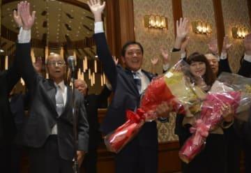 知事選で3選確実の報を受け、万歳する中村時広さん(中央)と妻の美由紀さん(右)=18日午後8時10分ごろ、松山市大街道3丁目の報告会場