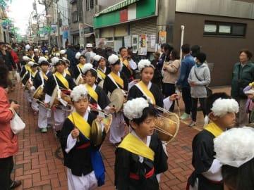 チャンゴなどの太鼓をたたきながらパレードする子どもたち=桜本商店街