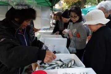 「ひろしま朝市」で魚を売る広島漁師の会のメンバー(左側)。新鮮な魚を食卓に届ける行商の伝統を受け継ぐ