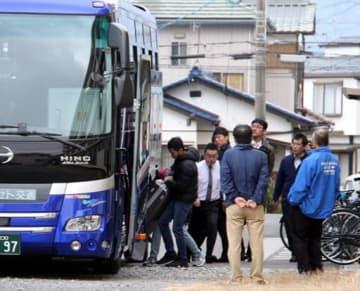 バスにスーツケースを積み、帰国の途に就くフィリピン人の元実習生たち