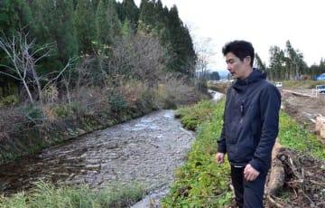 小水力発電所の工事現場に立つ西村社長。「川の水が澄んでいると流量が安定し、効率的に発電できる」と話す=鹿角市花輪字近江谷地
