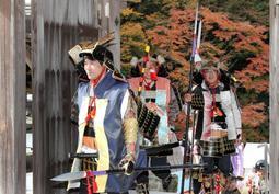 紅葉を背に、甲冑を身に着けて歩く武者行列の一行=荘厳寺