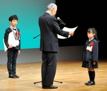 平山館長(中)から表彰される石光さん(右)。左は田中君