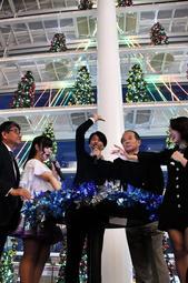 クリスマスツリーを点灯した蓬莱大介さん(中央)=あかし市民広場