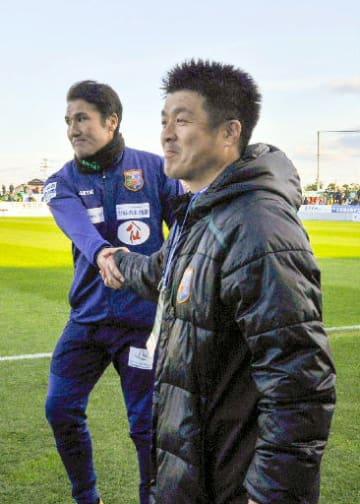 試合終了後、葛野昌宏監督(奥)と握手を交わす下平賢吾さん=18日、ダイハツスタジアム