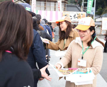 九年庵への来場者にパンフレットなどを手渡しする留学生ら=神埼市神埼町