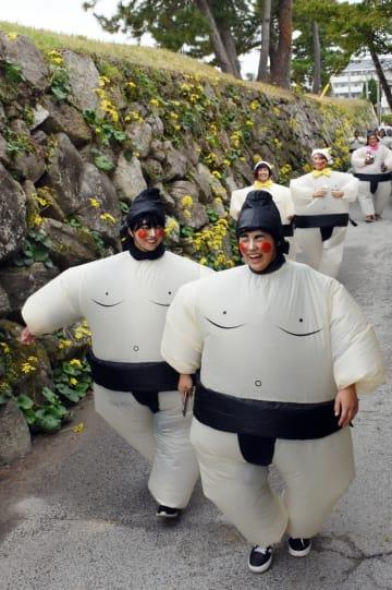 石垣の道を楽しそうに走る参加者たち=唐津市東城内