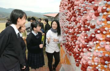 チョコレートで作ったアート作品「ビューティー」の前で話すジャニス・ウォンさん(右)と城北高生=山鹿市