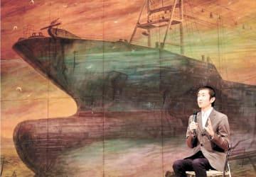共徳丸の水彩画をバックに思いを語る作者の加川さん